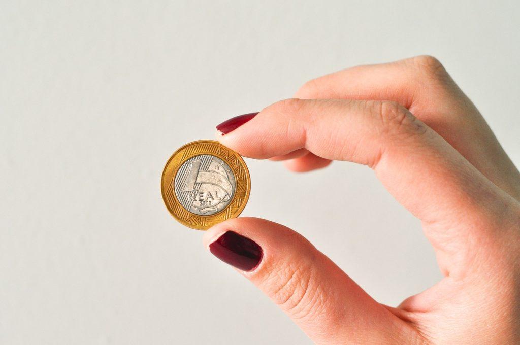Main qui tient une pièce de monnaie