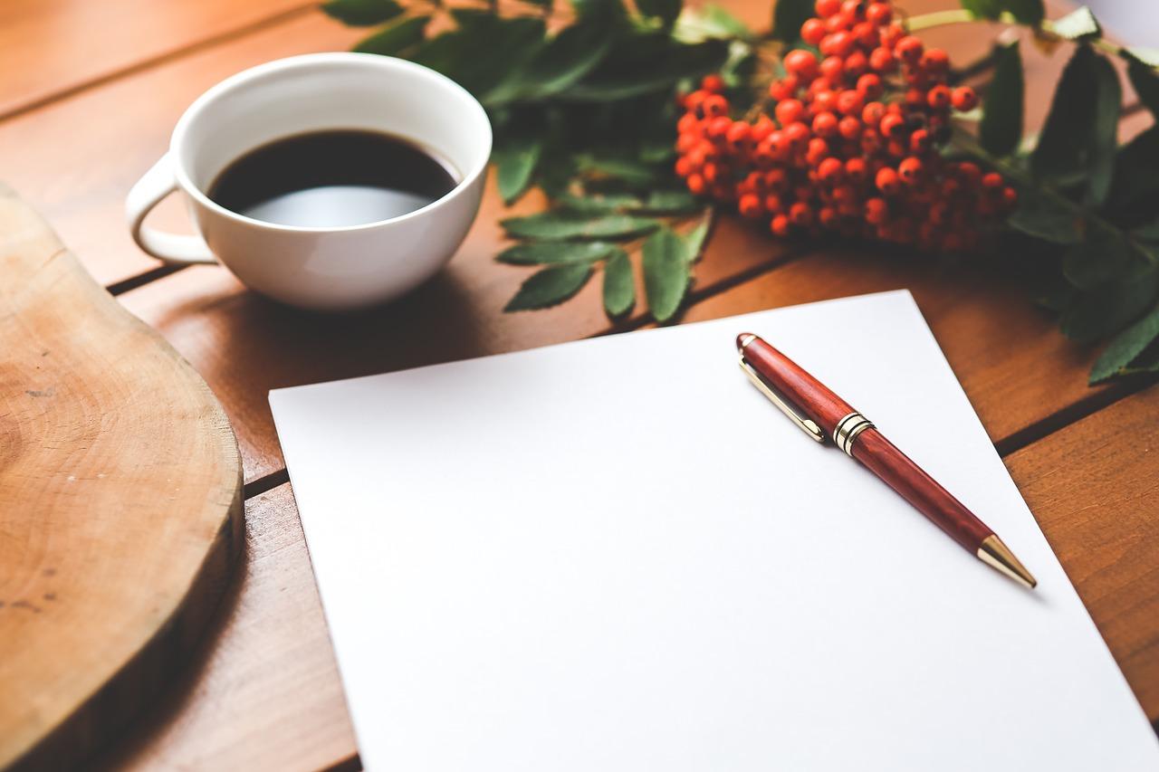 Tasse de café, bloc note et stylo au bureau