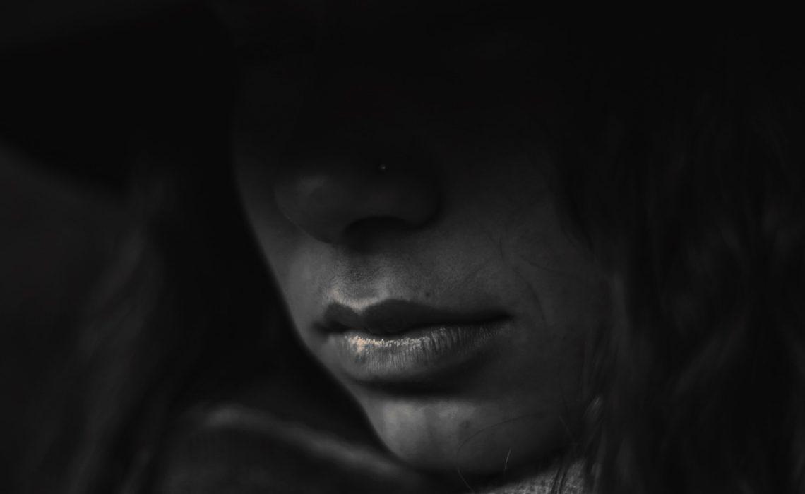 femme au visage caché honteuse