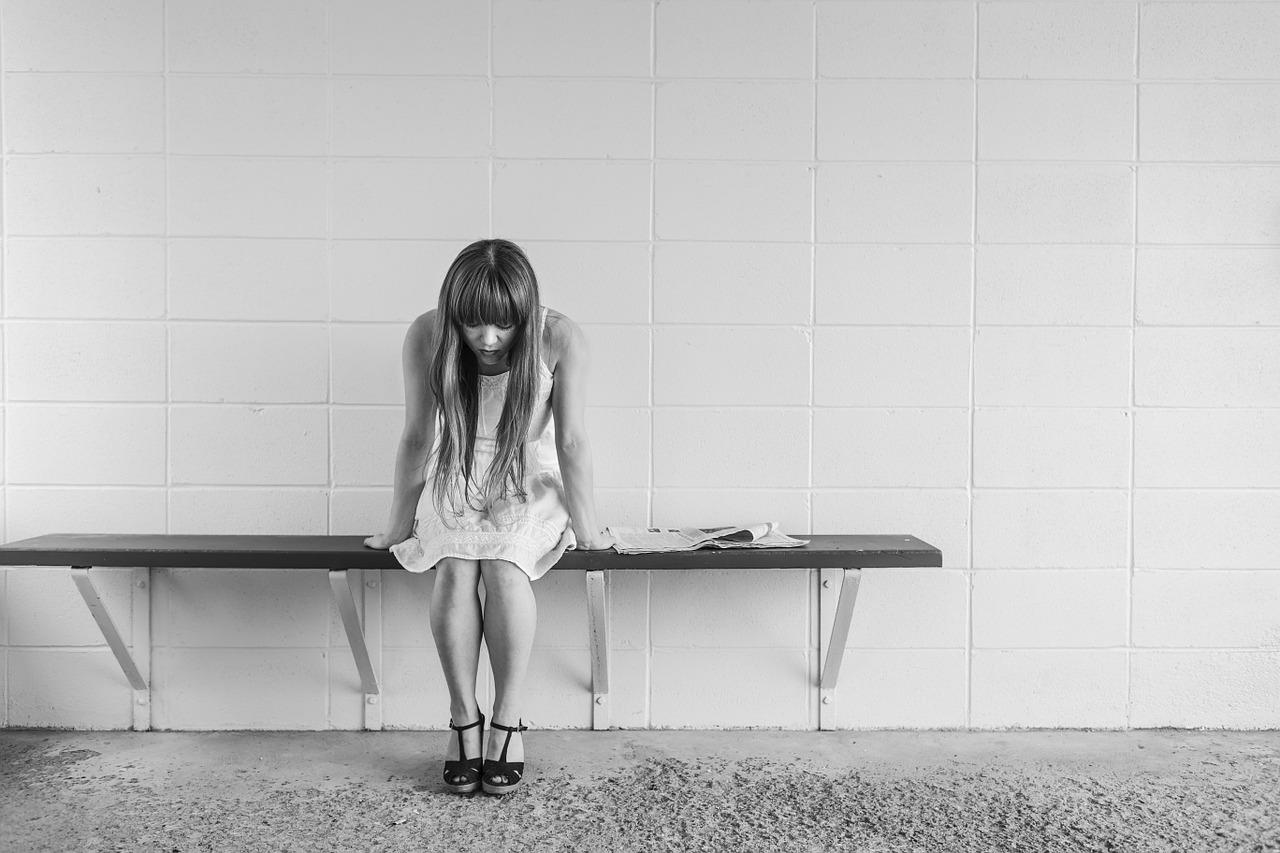 femme seule sur un banc la tête baissée