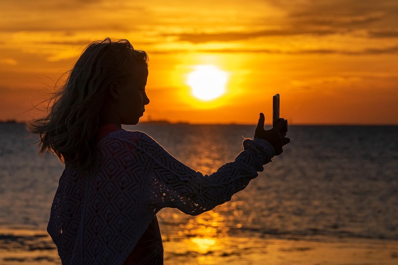 Une jeune fille de prend en photo sur la plage
