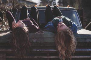 Femmes qui s'amusent sur un capot de voiture