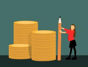 Femme qui mesure des piles de pièces de monnaie