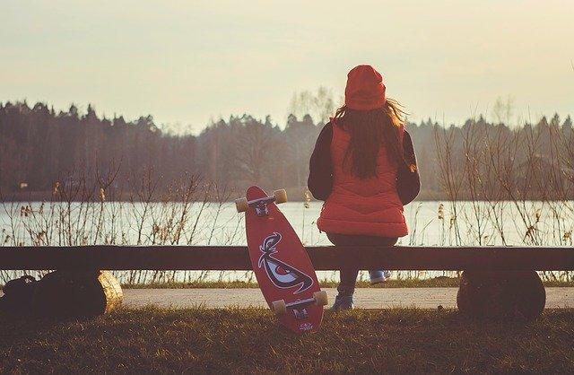 Femme assise sur un banc au bord d'un lac