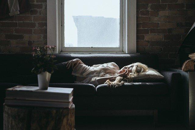 Femme couchée dans son canapé qui semble s'ennuyer