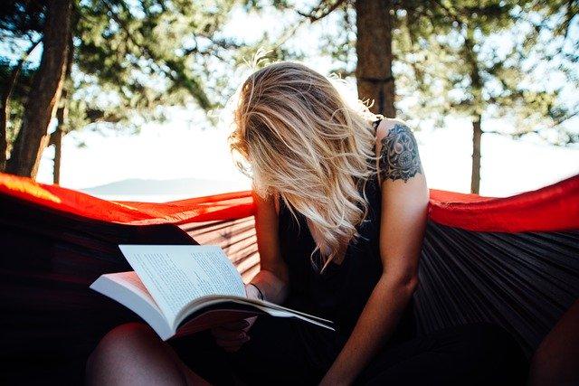 Jeune femme qui lit en extérieur