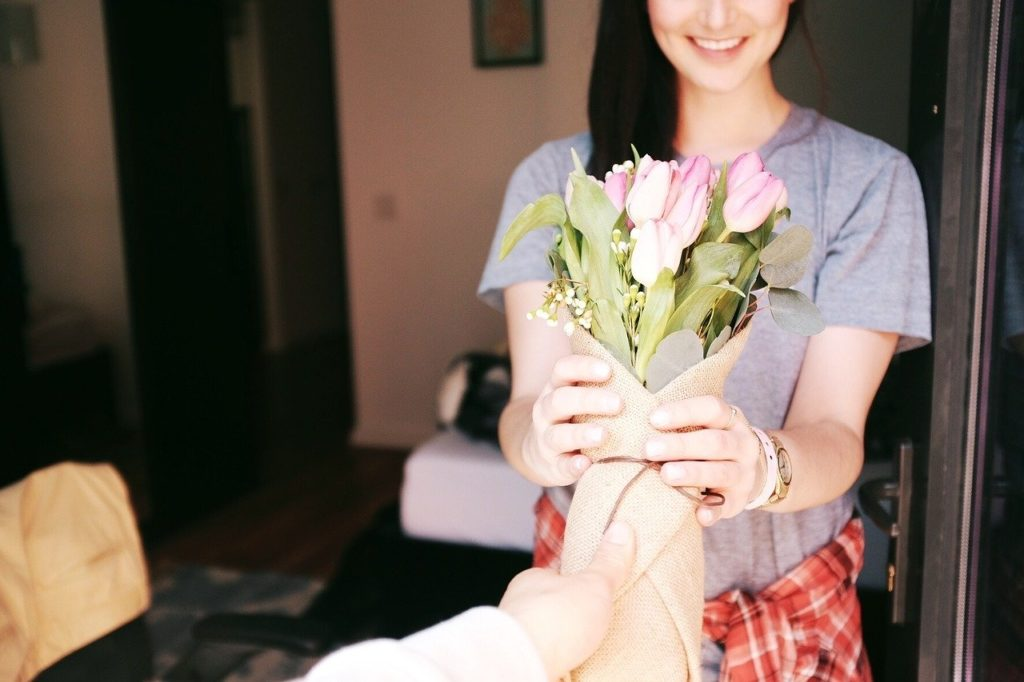 Femme souriante qui reçoit un bouquet de fleurs