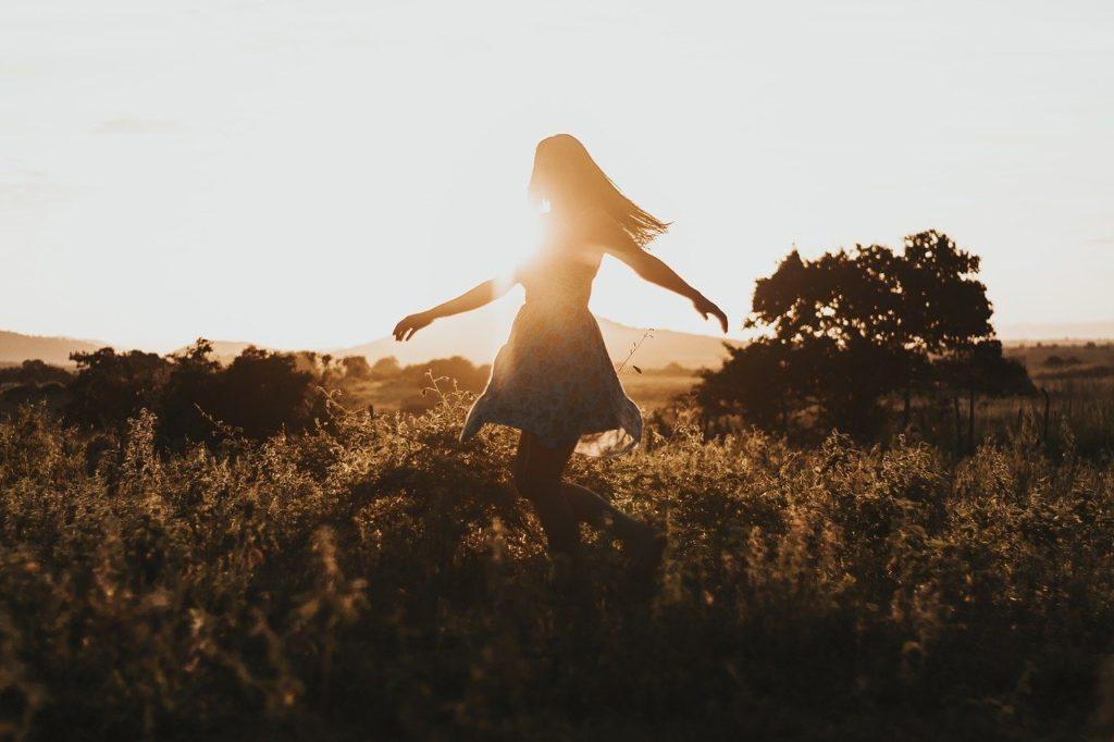 Femme joyeuse qui tourne sur elle-même dans la nature