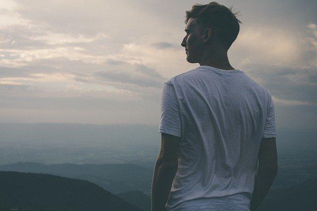 Homme en t-shirt blanc bras nus qui regarde l'horizon